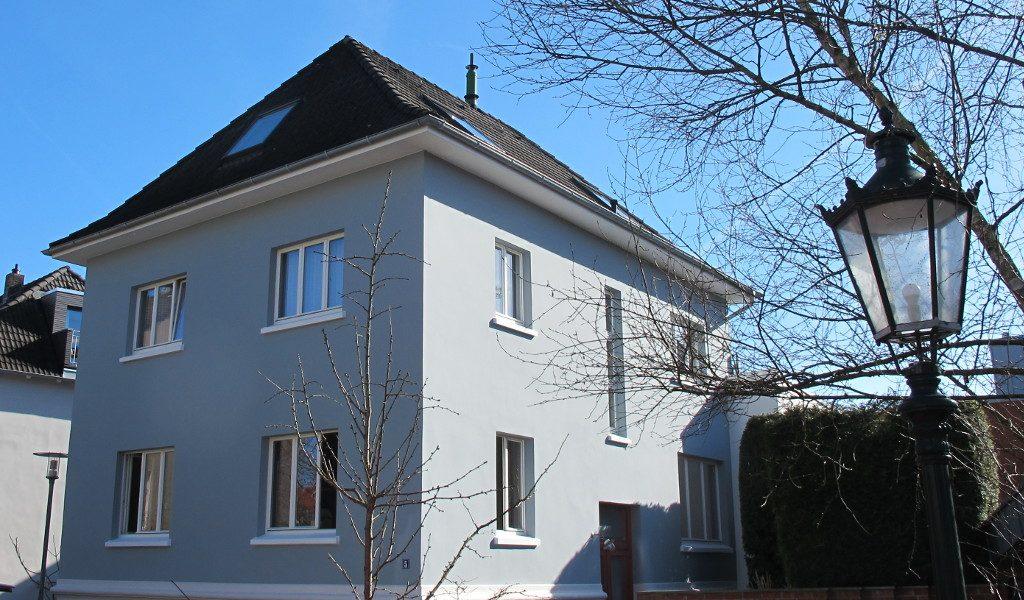 Stadthaus mit klaren, formschönen, weißen Holzfenstern von wfb mit einer Straßenlaterne