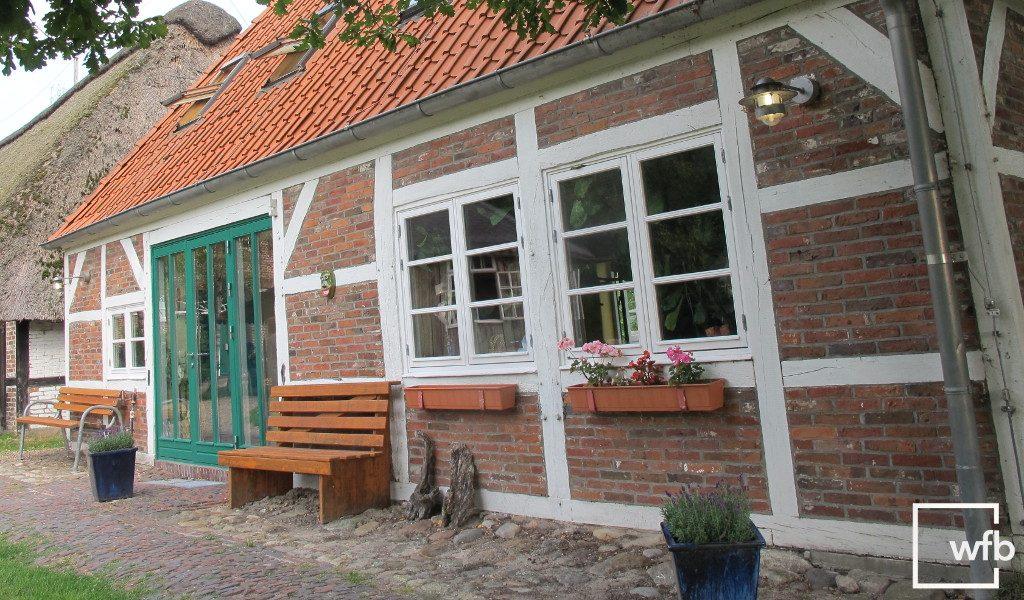 Bauernhaus mit Fachwerk und weißen Sprossenfenstern und grüner Fenstertür von wfb